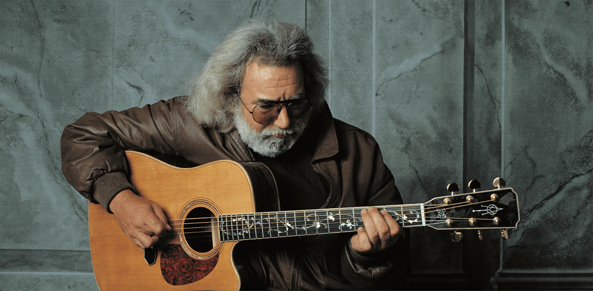 Gorgeous photo of Jerry Garcia taken by Herb Greene. He is sitting in a studio playing guitar. He is wearing jeans and a brown jacket.
